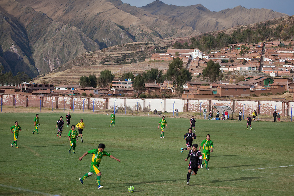 Football game between Chinchero and Machu Picchu teams, at Chinchero, with teh Andean mountains in the background, at Sacred Valley of the Incas, Peru