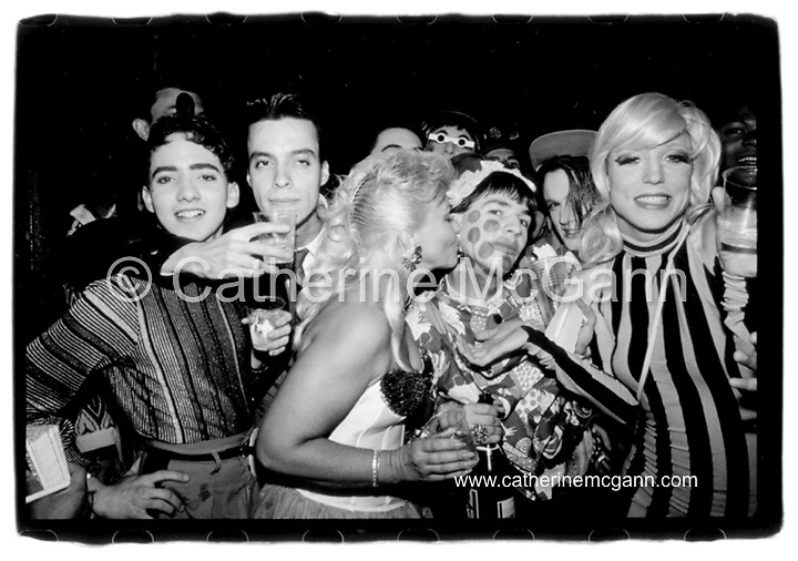 Michael Alig (second from right, with polka dot face) gets a kiss from his mother Elke at his birthday party at club Red Zone, New York City, 1989.  Drag queen Lahoma on right in striped dress.<br /> <br /> Copyright Catherine McGann / All Rights Reserved<br /> www.catherinemcgann.com<br /> catherinemcgann@gmail.com