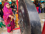 31 AUGUST 2014 - SARIKA, NAKHON NAYOK, THAILAND: A Hindu bangs a prayer gong during the Ganesh Festival at Shri Utthayan Ganesha Temple in Sarika, Nakhon Nayok. Ganesh Chaturthi, also known as Vinayaka Chaturthi, is a Hindu festival dedicated to Lord Ganesh. It is a 10-day festival marking the birthday of Ganesh, who is widely worshiped for his auspicious beginnings. Ganesh is the patron of arts and sciences, the deity of intellect and wisdom -- identified by his elephant head. The holiday is celebrated for 10 days, in 2014, most Hindu temples will submerge their Ganesh shrines and deities on September 7. Wat Utthaya Ganesh in Nakhon Nayok province, is a Buddhist temple that venerates Ganesh, who is popular with Thai Buddhists. The temple draws both Buddhists and Hindus and celebrates the Ganesh holiday a week ahead of most other places.    PHOTO BY JACK KURTZ