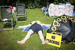 © Licensed to London News Pictures. 23/05/2016. Northallerton UK. Picture shows an anti fracking protester sunbathing at Northallerton County Hall. A decision is expected today at Northallerton County Hall on wether to allow UK firm Third Energy to frack for shale gas in Kirby Misperton. Photo credit: Andrew McCaren/LNP