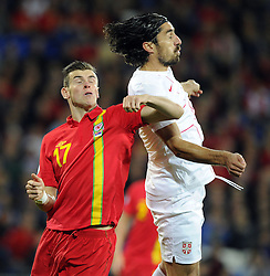 Gareth Bale of Wales (Real Madrid) battles for the ball with Milan Bisevac of Serbia (Lyon) - Photo mandatory by-line: Joe Meredith/JMP - Tel: Mobile: 07966 386802 10/09/2013 - SPORT - FOOTBALL - Cardiff City Stadium - Cardiff -  Wales V Serbia- World Cup Qualifier