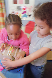 Nursery school girls playing with toy shop till in classroom,