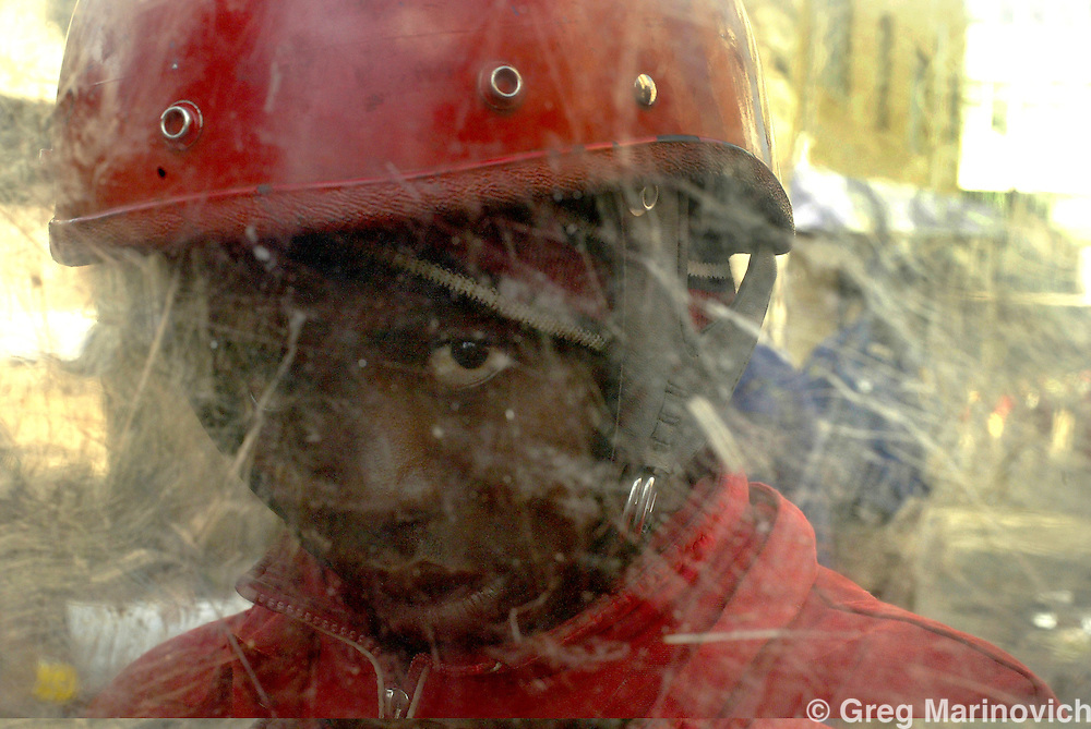 SOUTH AFRICA JOHANNESBURG July 14, 2005. Eighteen year old private security guard Thulani Ncube behind his shield on a 'Red Ants' security detail on Bree Street where several hundred people, including illegal Zimbabwean immigrants, were evicted from an office block being illegally used as apartments in downtown Johannesburg July 14, 2005. Johannesburg municipality uses the Red Ants to privatise the politically unpopular task of evictions of people living in unsuitable buildings and shanty towns. Many of the deserted or derelict downtown office and apartment blocks have been invaded by people desperate for low-priced living space. Greg Marinovich / Storytaxi.com