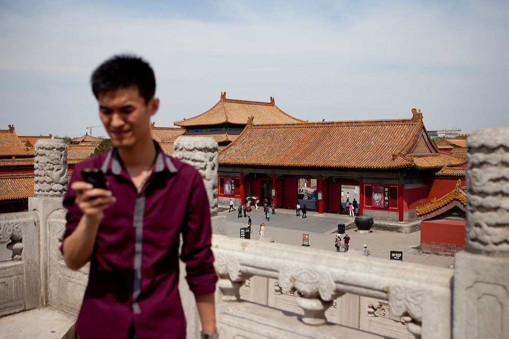 "Tourist watching his mobile phone inside  ""The Forbidden City"" which was the Chinese imperial palace from the Ming Dynasty to the end of the Qing Dynasty. It is located in the middle of Beijing, China. Beijing is the capital of the People's Republic of China and one of the most populous cities in the world with a population of 19,612,368 as of 2010."