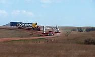 A pair of Cruz Energy Services heavy haul trucks move an oil rig's derrick to a new location in the Bakken field of North Dakota.