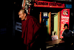 A monk makes his way through town of McLeod Ganj, Dharamsala, India, where the Dalai Lama settled after fleeing Tibet in 1959 after a failed uprising against Chinese rule, May 27, 2009.