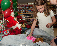Kaylee Jones gets some assistance from Vinette at Heath's Supermarket in Center Harbor after visiting with Santa Claus Friday evening.  (Karen Bobotas/for the Laconia Daily Sun)
