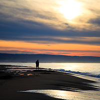 Photo of person walking on Balboa beach during sunrise in Newport Beach. Newport Beach is a wealthy beach community along the Pacific Ocean in Orange County Southern California.
