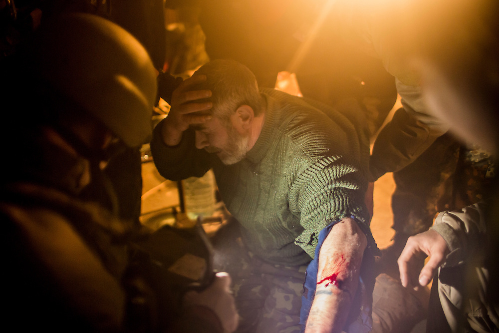DEBALTSEVE, UKRAINE - FEBRUARY 8, 2015: An ambulance driver named Tariel, a Ukrainian Army medic, is treated for a shrapnel wound to the arm received during shelling near a medical treatment point for Ukrainian fighters in Debaltseve, Ukraine. Fighting between pro-Russia rebels and Ukrainian forces there over the past two weeks has dealt steady casualties to Ukrainian fighters and civilians. CREDIT: Brendan Hoffman for The New York Times