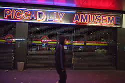 © Licensed to London News Pictures. 10/08/2011. Salford, UK. A hooded man walks by the broken grilles of Piccadilly Amusements. Scenes of desctruction in Manchester, where people rioted and looted and premesis were set alight. Photo credit : Joel Goodman/LNP