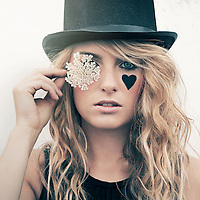 young woman with blonde hair wearing a top-hat and holding a flower in front of her eyes
