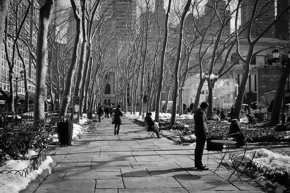 Winter in New York can be bitterly cold. A man catches some quick rays during lunch hour, to warm up and recharge in Bryant Park NYC.