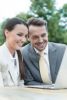 Happy businesspeople using laptop outdoors