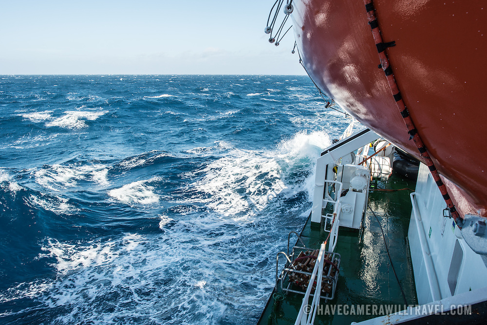 A stiff breeze whips up chop and waves on Drake Passage between South America and Antarctica in the Southern Ocean. Seen from the deck of a ship, with part of a bright orange lifeboat in the top right corner of frame.