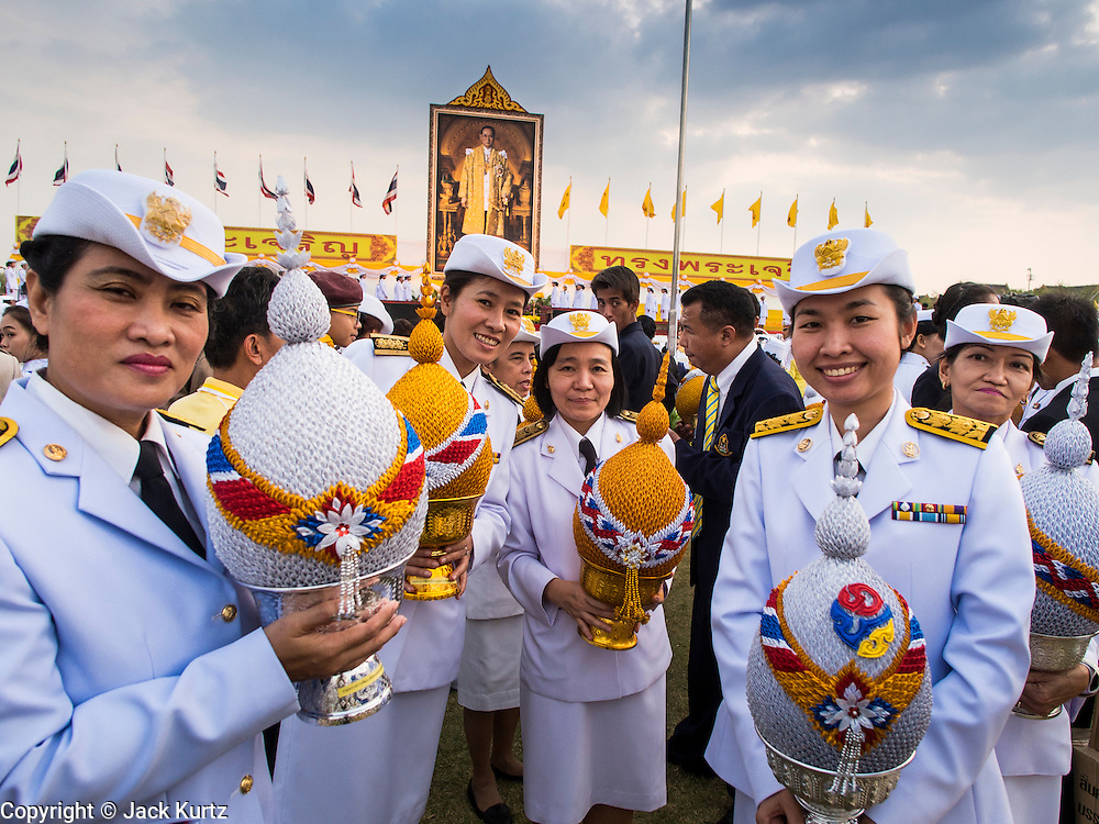 05 DECEMBER 2013 - BANGKOK, THAILAND: Thai civil servants with offerings for the King during the celebration of his birthday. Thais observed the 86th birthday of Bhumibol Adulyadej, the King of Thailand, their revered King on Thursday. They held candlelight services throughout the country. The political protests that have gripped Bangkok were on hold for the day, although protestors did hold their own observances of the holiday. Thousands of people attended the government celebration of the day on Sanam Luang, the large public space next to the Grand Palace in Bangkok.     PHOTO BY JACK KURTZ