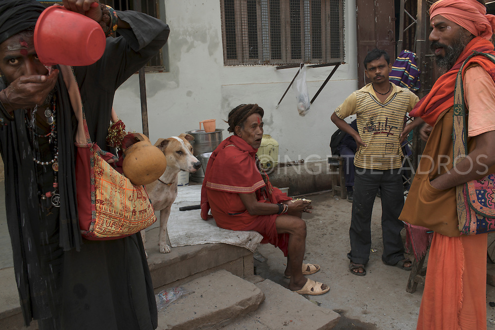 Rahm (L) and his dog Calu, Baba G (Sitting) and Kopal (R) just finished lunch at a local Varanasi food-store. India.