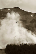 Helicopters drop water on a wild fire on the slopes of Blackcomb Mountain.  Whistler BC, Canada.