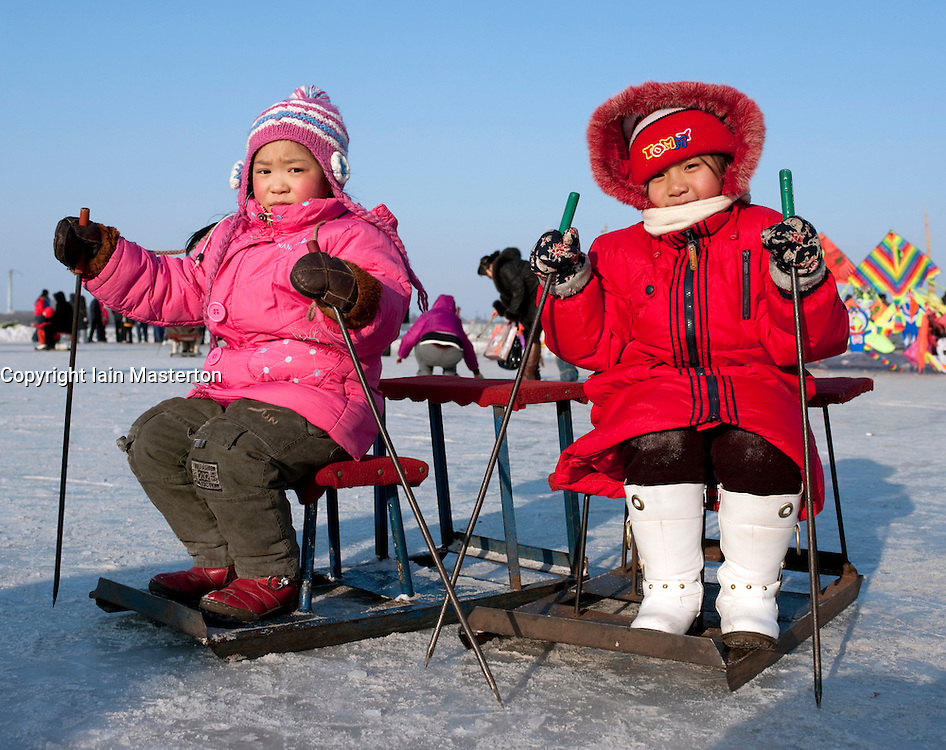 Two young Chinese girls on old fashioned sleds on frozen Songhua River in Harbin during winter 2009