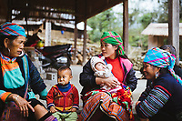 Hmong women and children sit around outside the Waterfall Homestay in Giang Ta Chai village, about 18km from Sapa in northern Vietnam.