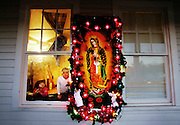 A shrine to the Virgin of Guadalupe was set up outside a home on Bluff road. The Virgin is the Mother of all Mexicans, protectress of all the poor and a constant guardian. As each December approaches, Mexicans throughout the world pay tribute to her. The Virgin was adorned by lights and angels. Inside the two-story home Alicia Tapia Cervantez, left, 2, and Diana Tapia, 6 looked out their window. More Hispanic families are moving into Olympia and calling the area home thus changing the area's landscape.