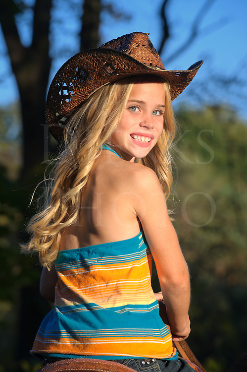 Pretty blonde cow girl horseback riding wearing a cowboy hat, looking back over her shoulder, photographed in last of afternoon golden light, summer in Pennsylvania, USA.