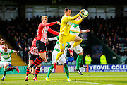 Yeovil Town's Artur Krysiak jumps to claim the ball from a cross beating Exeter City's Jayden Stockley to it during the Sky Bet League 2 match between Yeovil Town and Exeter City at Huish Park, Yeovil, England on 9 April 2016. Photo by Graham Hunt.