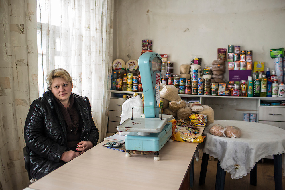 GOLOTARSKOGO, UKRAINE - JANUARY 24, 2015: Yelena Nesterenko poses for a picture sitting behind the counter in the small shop where she sells essential items in Golotarskogo, Ukraine. Due to fighting, many residents have difficulty reaching shops in other towns; the store in Golotarskogo is located in the house of a family that moved away. CREDIT: Brendan Hoffman for The New York Times