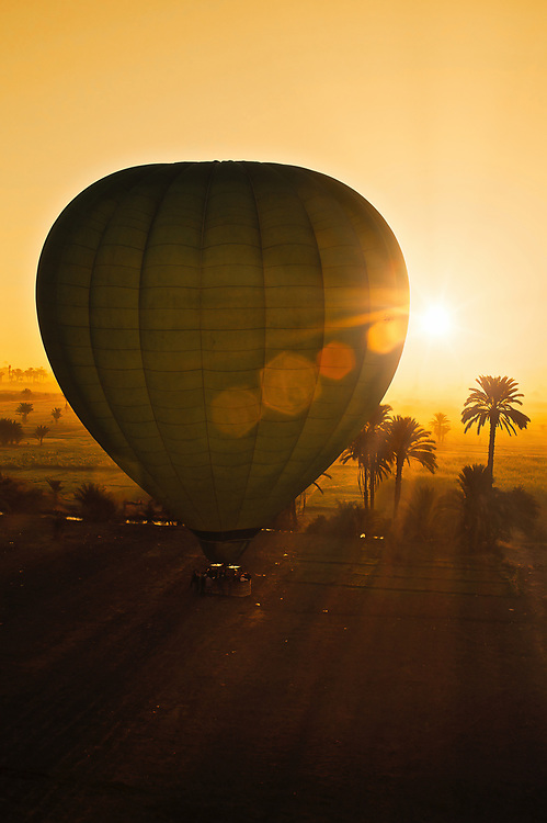 Morning Sun. Sunlight reaches around the giant balloons rising out of the morning mist and shadows.