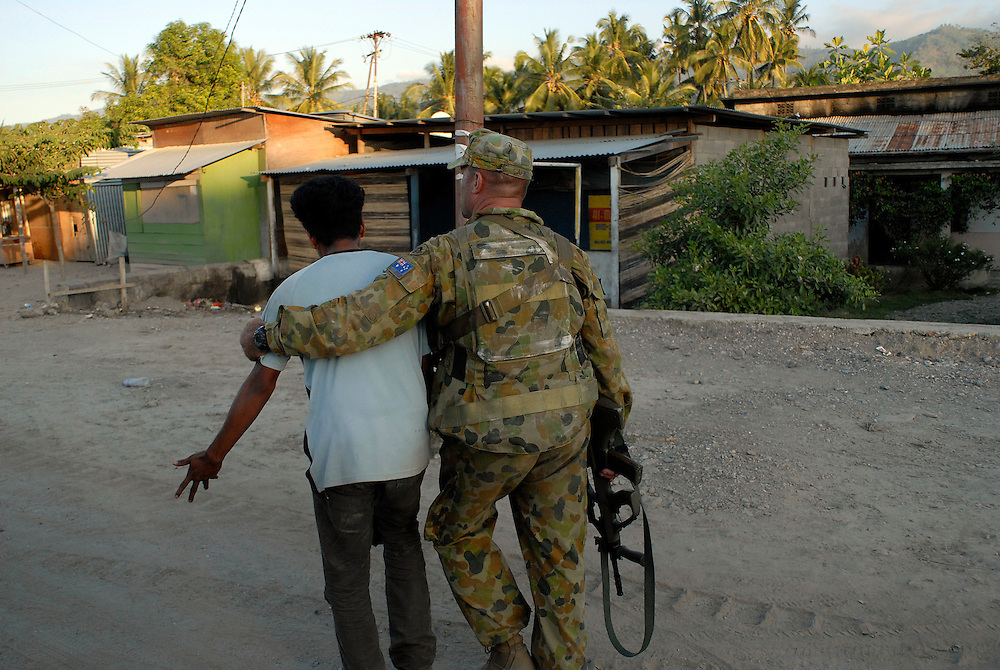 After losing his house and belongings to a random act of arson at Comora, a young man is comforted by an Australian soldier outside the location of Prime Minister Mari Alkatiri's party meeting and press conference. Comora, Dili, East Timor 04/06/06