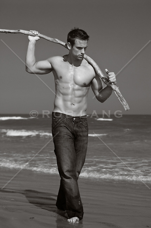 shirtless man walking with a tree branch behind his neck at the ocean