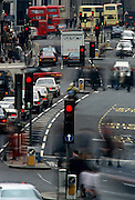 From a slightly raised viewpoint we are looking up Bishopsgate Street in the oldest area of Britain's capital, the Square Mile in the City of London. As traffic is at a standstill when lights are red, pedestrians to and fro across the scene, blurring as they negotiate crossings and traffic islands mid-way across this old Roman and medieval highway that travels north-south in what is now the city's financial district. Buses can be seen in the far distance too adding to the general bustle of a busy metropolis. The highway tends to zigzag into the distance and with the foreshortening of a long lens, appears to have a compressed perspective.