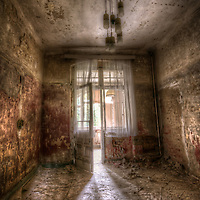 Abandoned hotel with decaying interior and sunlight shining through doors with net curtains