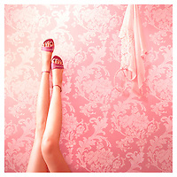 A young woman showing long legs wearing pink shoes against pink wallpaper