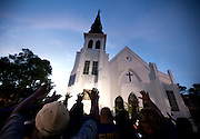 The men of Omega Psi Phi Fraternity Inc. lead a crowd of people in prayer outside the Emanuel AME Church, Friday, June 19, 2015 after a community prayer and healing vigil in Charleston, S.C. Thousands gathered at the College of Charleston TD Arena to bring the community together after nine people where shot to death at the church on Wednesday. (AP Photo/Stephen B. Morton)