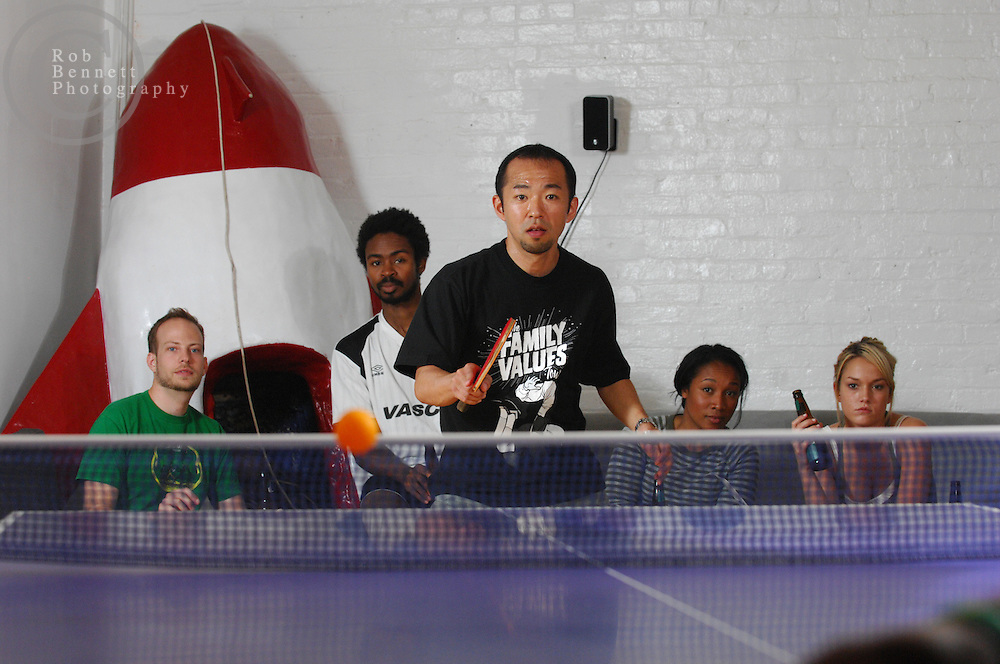 "Here, Kazuyuki Yokoyama, a former professional player in Japan, plays a match while a group watches in the background. .---.New York, NY- Friday, August 10, 2007 - ""Naked"" Ping Pong Tournament/Party-  An eclectic collection of city residents gather for a recurring Friday-night table tennis tournament/party at the Naked Ping Pong Club in the TriBeCa area of Manhattan. The founders of Naked Ping Pong are a trio of filmmakers (most recently, Naked Yoga) - Bill Mack, 34, Franck Raharinosy, 32 and Jonathan Bricklin, 30 - who claim to be training for the 2012 Olympics in London.. .Credit: Rob Bennett for The New York Times"