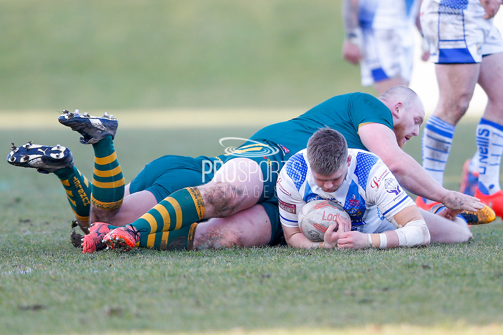 Workington Town loose forward Joseph Ryan (13) is stopped by Hunslet Club Parkside prop Jamie Fields (10)  during the Ladbrokes Challenge Cup round 3 match between Hunslet Club Parkside and Workington Town at South Leeds Stadium, Leeds, United Kingdom on 24 February 2018. Picture by Simon Davies.
