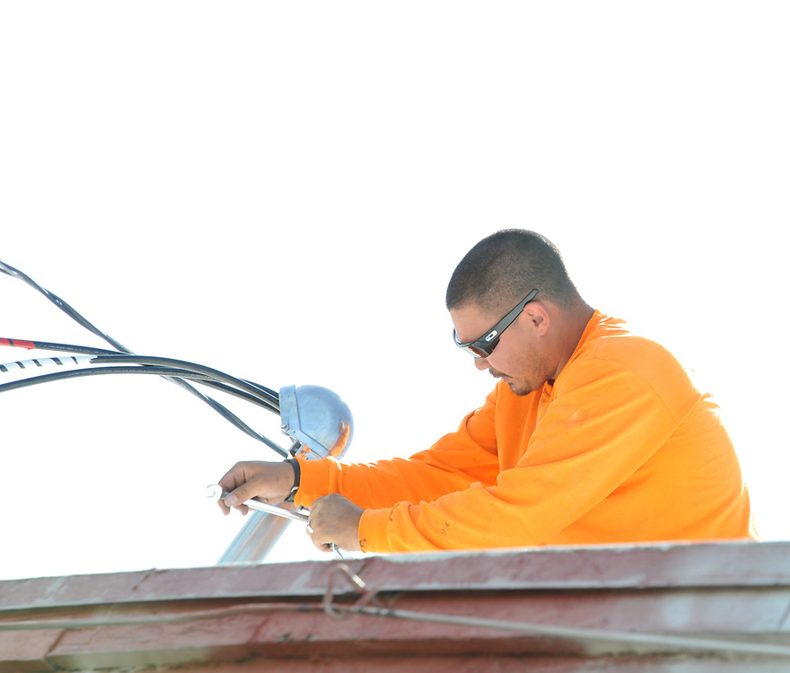 Lytle Electric worker installs service mast.