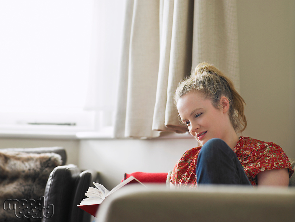 Woman sitting in living room reading book