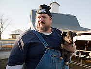 Carl Blake holds a young Iowa Swabian Hall Boar on a finishing farm in Iowa on Thursday, December 13, 2012.