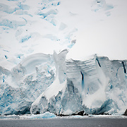 "Steep cliffs of a glacier line the side of the Lemaire Channel on the western side of the Antarctic Peninsula. The Lemaire Channel is sometimes referred to as ""Kodak Gap"" in a nod to its famously scenic views."