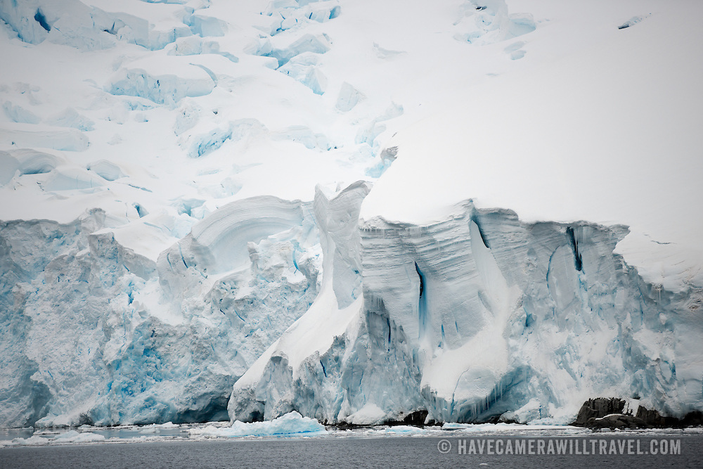 """Steep cliffs of a glacier line the side of the Lemaire Channel on the western side of the Antarctic Peninsula. The Lemaire Channel is sometimes referred to as """"Kodak Gap"""" in a nod to its famously scenic views."""