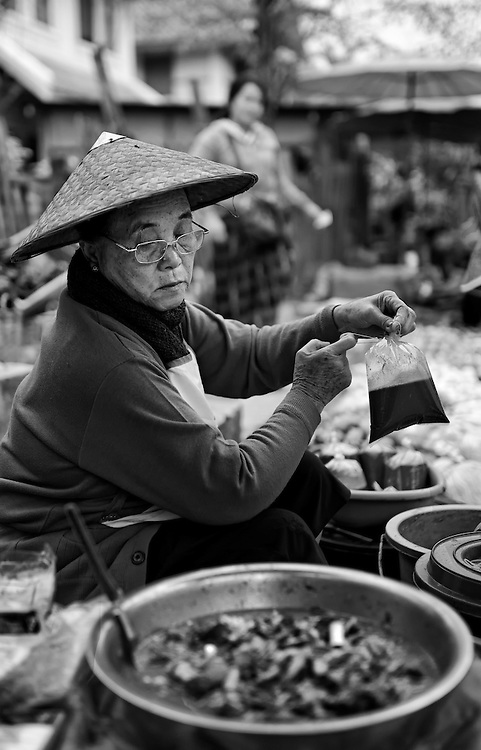 A woman selling padek in the morning market in Luang Prabang, Laos.