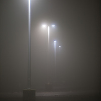Parking lot lights glow in a cloudy has as fog rolled into the parking lot of the Belford NJ Ferry Terminal.