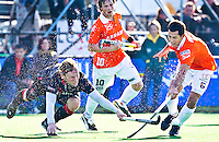 BLOEMENDAAL - Robert Tigges (L) van Amsterdam in duel met Bloemendaal-speler Jamie Dwyer,zondag tijdens de competitie wedstrijd hockey bij de mannen tussen Bloemendaal en Amsterdam (3-1). In het midden Roelk Bovendeert van Bloemendaal.  COPYRIGHT KOEN SUYK