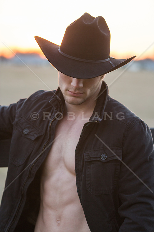 cowboy with an open shirt at sunset