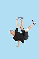 Break dancer performing handstand over blue background