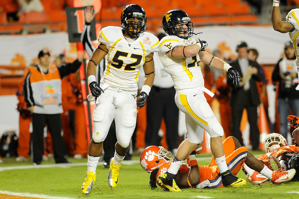 January 4, 2012: Najee Goode #52 and Jared Barber #33 of West Virginia react after tackling Andre Ellington #23 of Clemson during the NCAA football game between the West Virginia Mountaineers and the Clemson Tigers at the 2012 Discover Orange Bowl at Sun Life Stadium in Miami Gardens, Florida.