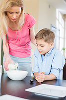 Mother pouring milk for son at table