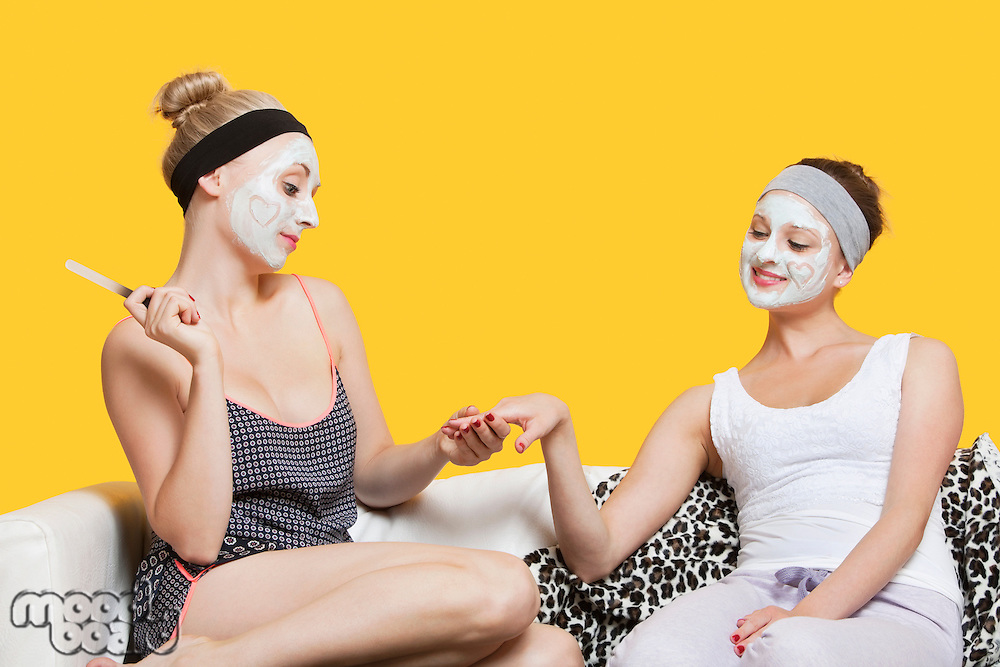 Young woman with face pack filing friend's nails while sitting on sofa over yellow background