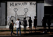"""People pay their respects at the """"Hi, How Are You"""" mural created by musician and artist Daniel Johnston on Wednesday, Sept. 11, 2019, in Austin, Texas. Johnston died at the age of 58 Wednesday morning. [NICK WAGNER/AMERICAN-STATESMAN]"""